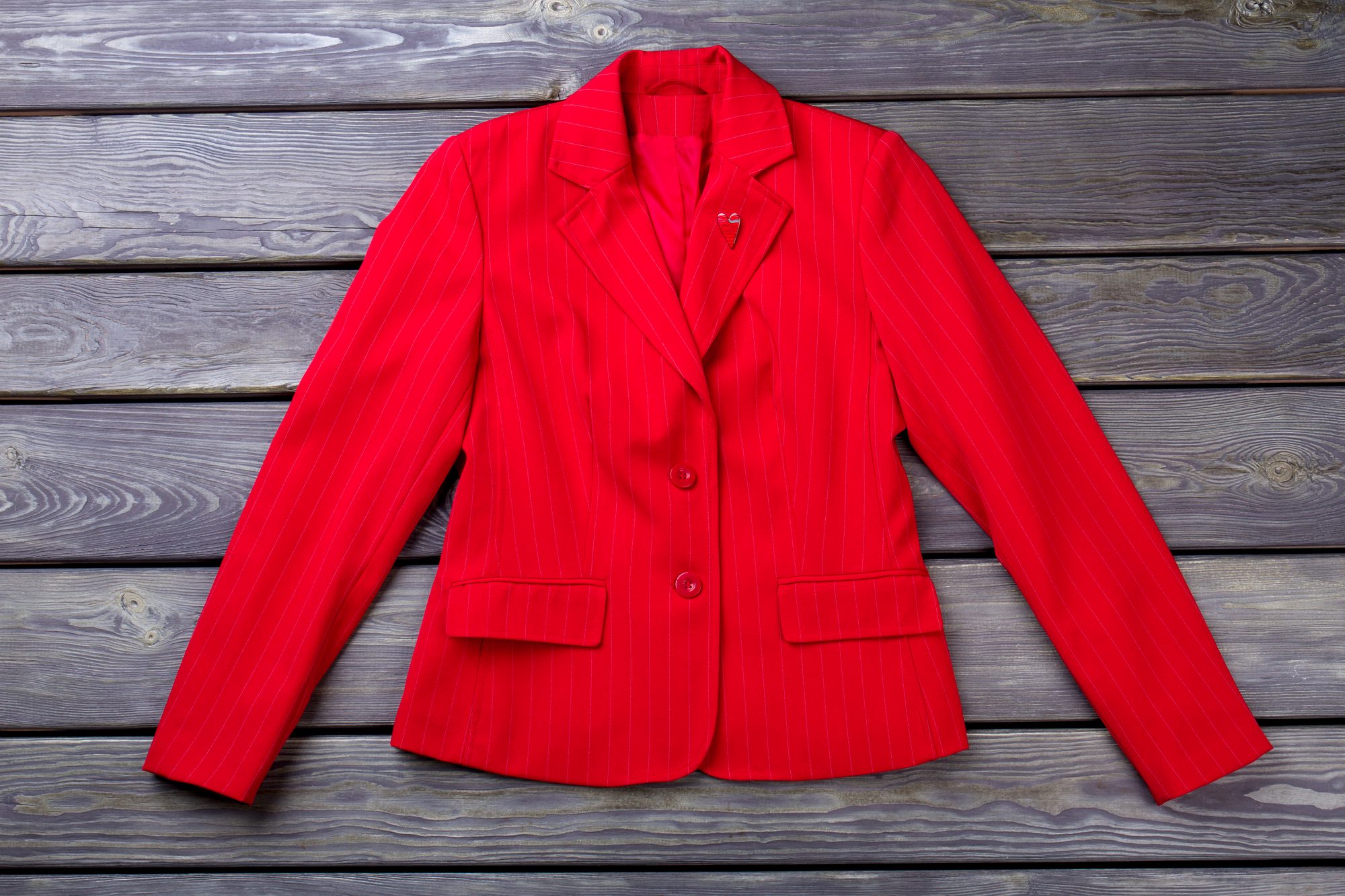 Flat lay red jacket. Women's suit, grey wooden surface background.